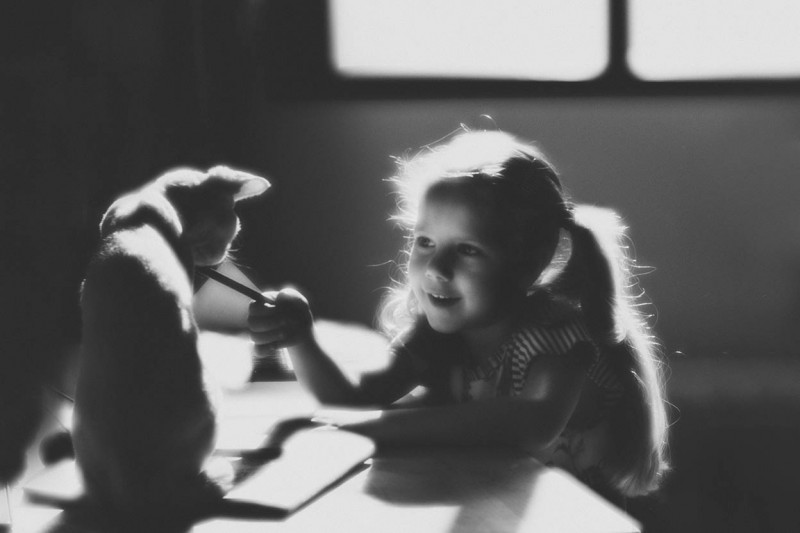 Young girl playing with a cat (shot with Lensbaby's Velvet 56 lens)