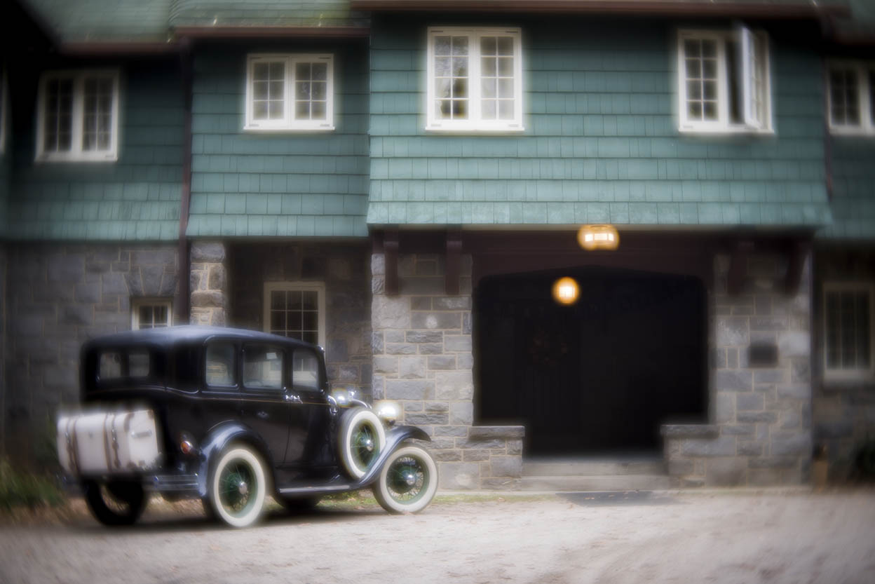 Classic car in front of a country home