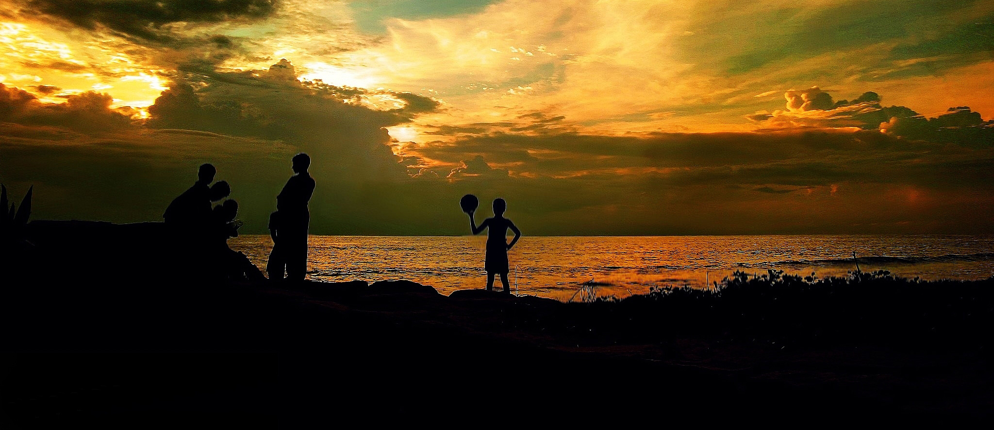 Silhouettes of people playing football at sunset