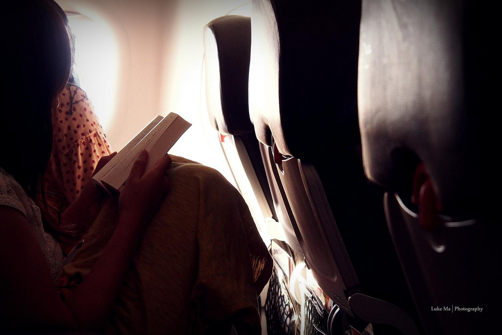 Girl Reading Book on Airplane