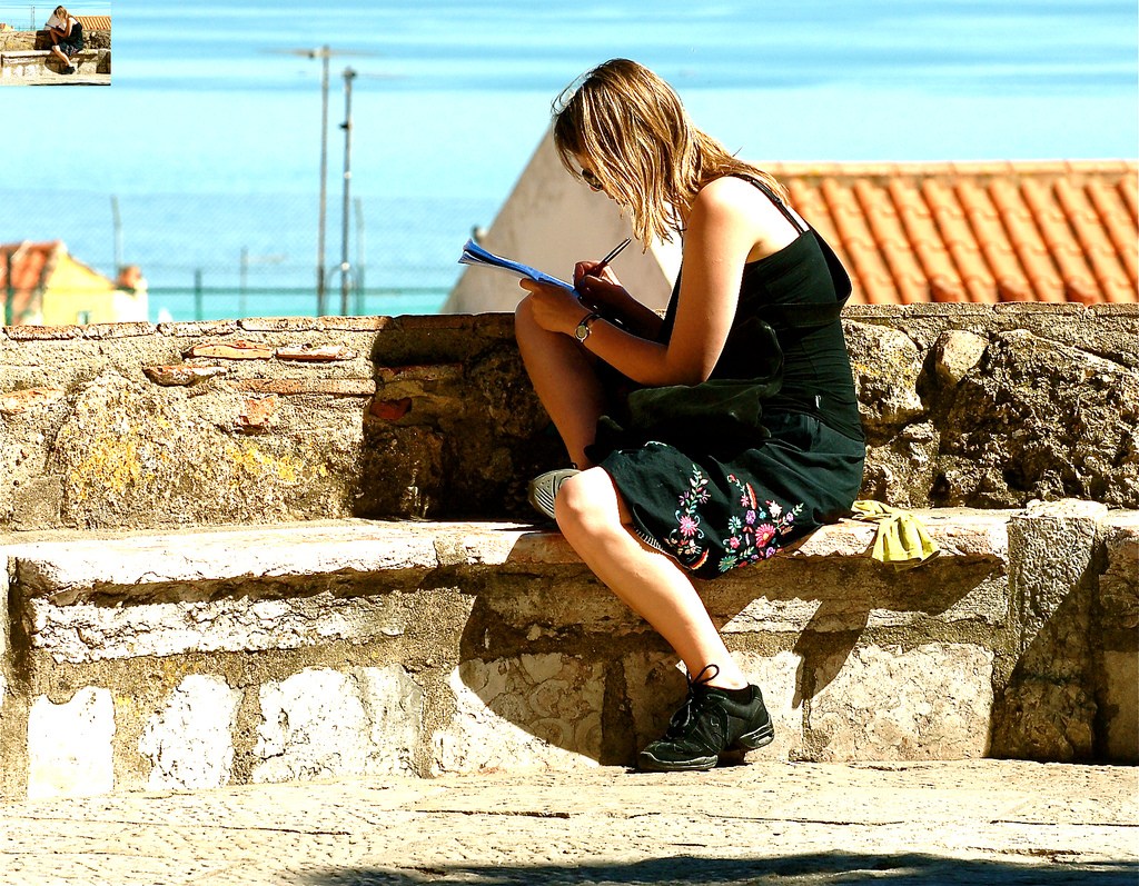 Girl writing in notebook, Lisbon, Portugal