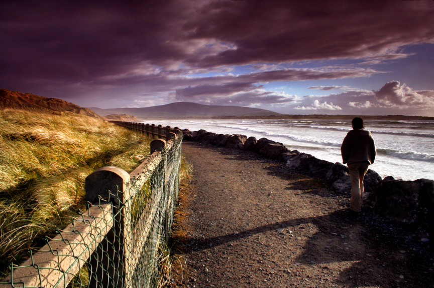 Woman hiking along shore in Sligo, Ireland