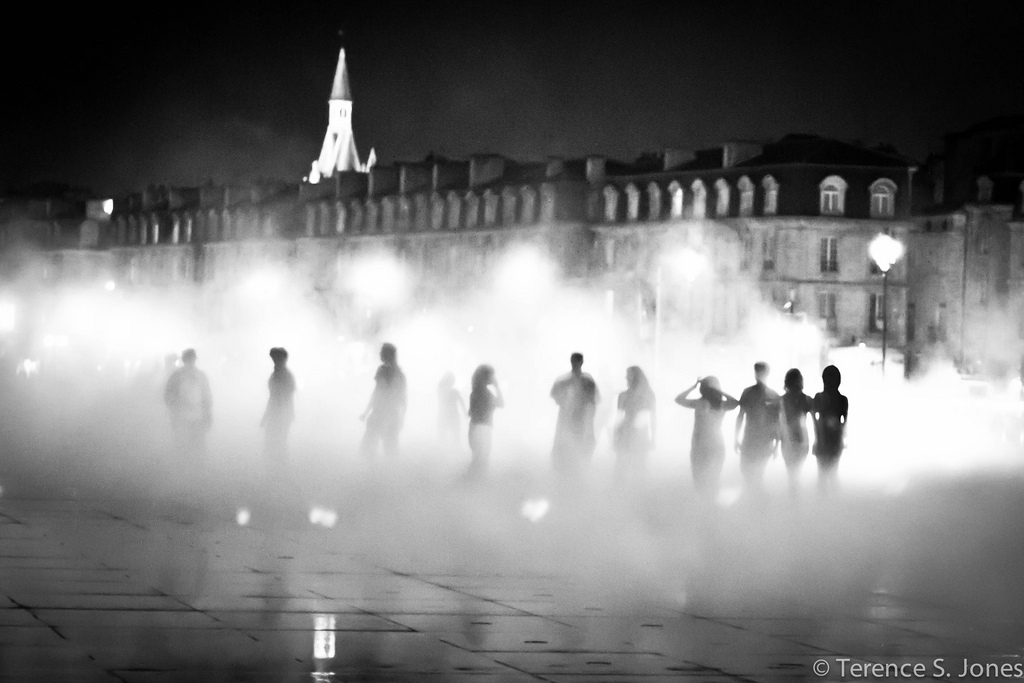 People standing in the mist of a fountain in Bordeaux, France