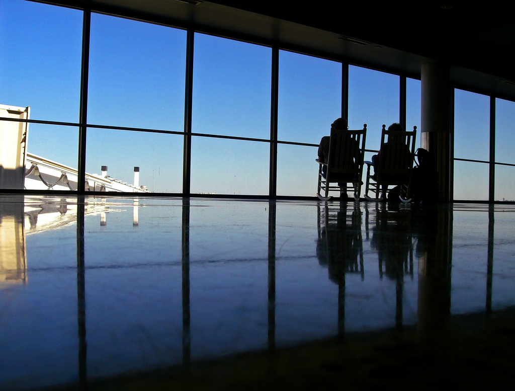 Two people relaxing in chairs at Boston's Logan Airport
