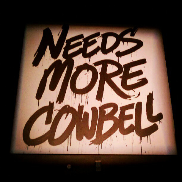 """Needs more cowbell"" (sign)"
