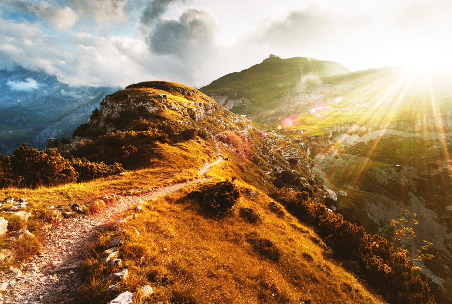 Sunlight illuminating mountain path in the alps, Switzerland