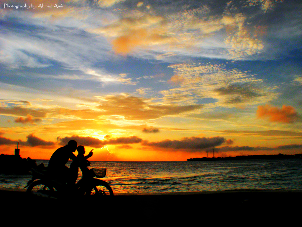Silhouette of two people on bikes in front of a sunset in Maldives