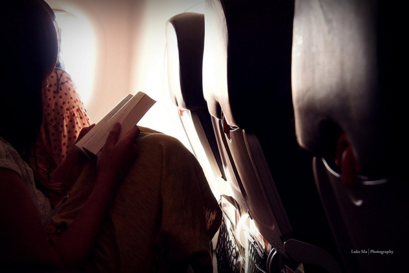 Woman reading book on airplane