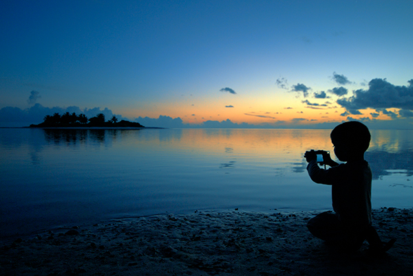 Young boy photographing beach in Maldives